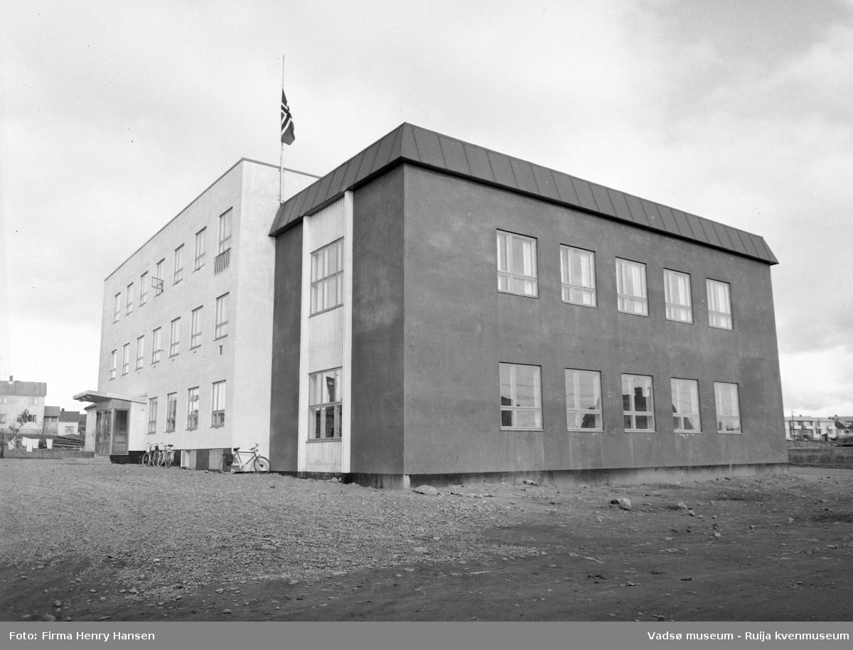 Vadsø 1957. Bildet viser Vadsø Samfunnshus og er tatt mot nordøst. Det står parkerte sykler langs veggen mot vest. I bakkant av bildet, på begge sider av samfunnshuset ser vi litt av bebyggelsen langs Idrettsveien. Flaggstangen på samfunnshuset er heist med flagget på halv stang.