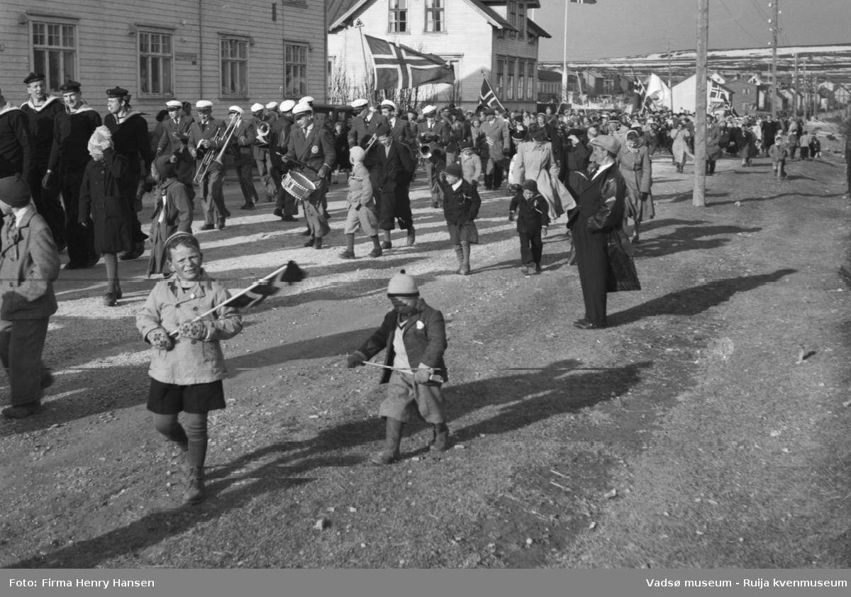 Vadsø 17 mai 1951. Bildet er tatt mot øst. 17.maitoget, muligens folketoget, marsjerer i Ytrebyen. I høyre bakkant av bildet ser vi Melkevarden, litt snedekket,  I venstre billedkant, foran i toget, ser vi noen marinegaster. Rett bak kommer musikkorpset marsjerende. Folk og barn med flagg sees i og langs toget,