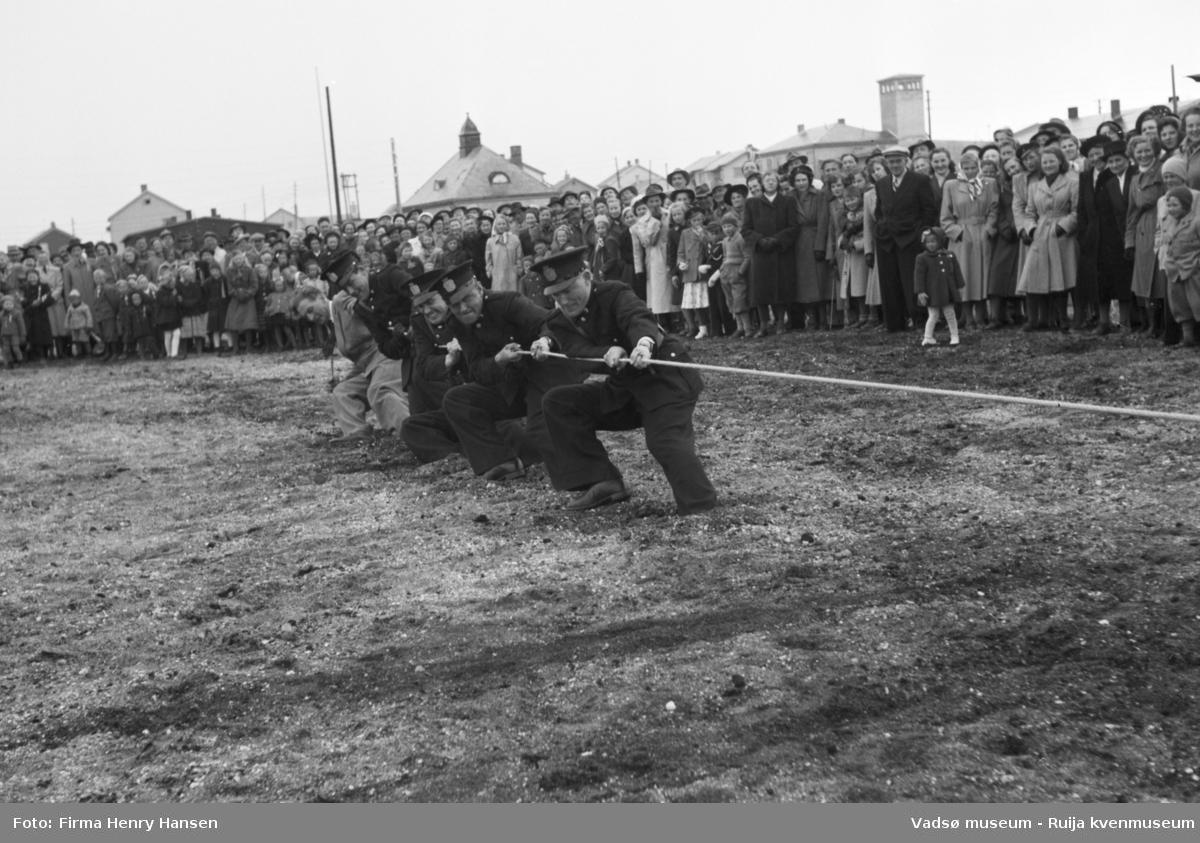 Vadsø 17 mai 1951. Tautrekkingkonkurranse, muligens på idrettsplassen. I enden av tauet ser vi fem menn, fire i politiuniform, som trekker i tauet. En stor menneskemengde, barn og voksne, kvinner og menn, står og bivåner det hele.  I bakkant av bildet ser vi bygninger, bl.a. tårnet og deler av brannstasjonen og taket til Finnmarksbiblioteket.