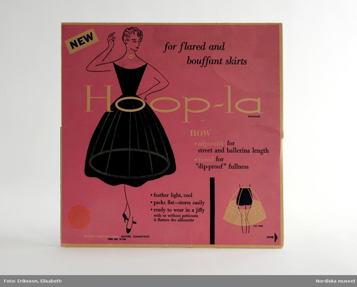 """Förpackning med underkjolsställning från 1950-talets andra hälft, Hoop-la. Ställningen användes för att hålla ut kjolens vidd. Den nedre delen av bomullstyg har sydda kanaler upptill och nedtill. Där träs medföljande ståltrådar in. Fem bomullsband förbinder nederdelen med en midjeresår. Banden är reglerbara med tryckknappar, för olika kjollängder. Ett annat, enklare sätt var att ta en eltråd, isolerad med plast, och trä in i fållen på en vanlig underkjol. /Utställningstext """"Mitt 50-tal"""" 2017"""