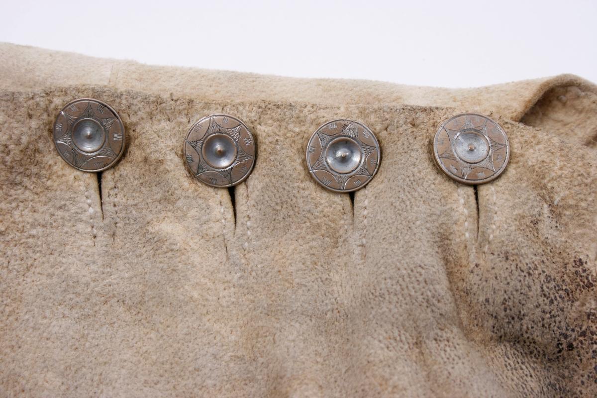 Håndsydd knebukse i lyst skinn. Lav midjeplassering. Linningen i midjen og lokket lukkes med ulike og graverte messingfargede knapper.  I høyre side ved linningen er det innsydd en lomme. I linningen MB er det splitt som lukkes med skinnsnor gjennom 3 x 2 hull og MF lukkes den med 3 knapper. Linningen er foret med ullstoff og har 4 rader prikkestikning gjennom for og skinn. Stor vidde over baken. Nede ved knærne er det splitter som lukkes med 4 knapper. Påsydd knelinning som trolig har hatt spenne for lukking. Alle knappene er festet med skinnsnor som igjen er festet på innsiden av plagget.Alle sammensyingskanter har tittekanter.