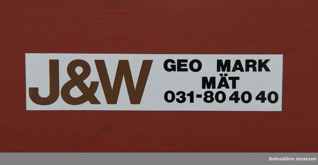 Funktionsmodell för fällning av Uddevallavarvets 900 ton tunga bockkran.  Skala 1:100. Kranen är rödmålad med en grå sockel. Fällbara delar i gångjärn som stagas upp med linor. Modellen är tillverkad av ingenjörsfirman KADO, Kent Adolfsson i Kungälv. På ena sidan etikett med texten: J & W GEO MARK MÄT 031 - 80 40 40