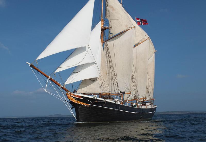 """Skonnerten """"Svanen"""" med tre master og for fulle seil ute på vannet, med norsk flagg, sett fra babord."""