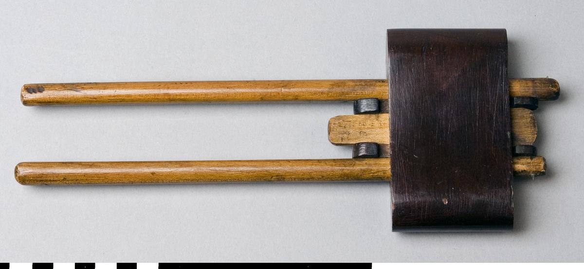 Strykmått av trä. Strykmåttet består av en klots av brunlackat trä genom vilken två pinnar av björk löper. I samma riktning mellan pinnarna löper en skjutbar kil för låsning av pinnarna för rätt mått. I ena änden av varje pinne sitter ett stift av stål för påritning av mått på arbetsstycke. Klotsen utgör anslaget.  Funktion: Ritsa avståndsmått på arbetsstycken, inställningsbar