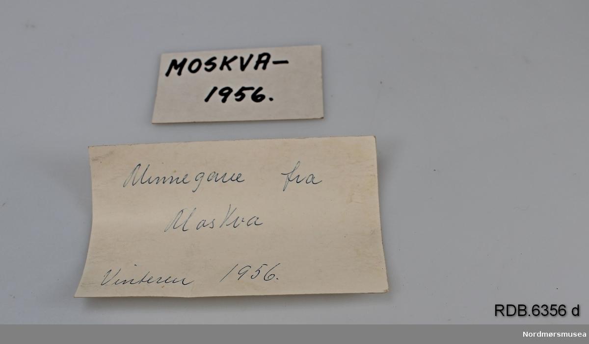 """Et tesett som består av en koppholder med hank og en teskje i sølvplett. Koppen har gjennombrutt mønster og dekor. Settet ligger i en brun gaveeske der lokket er trukket med gullfarga stoff og bunnen i blå silke. Eska er hengslet bak og har lås foran. I lokket et rundt felt med russisk påskrift i svart. I eska ligger to løse lapper med håndskrift: """"Moskva 1956- Moskova 1955"""" og """"Minnegave fra Moskva vinteren 1956""""."""