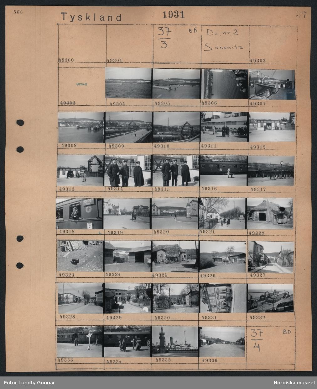 Motiv: Tyskland, Sassnitz; Vy över kust, hamn med fartyg, tre män i uniform, järnvägsstation med tåg, stadsvy med fotgängare, bondgård,