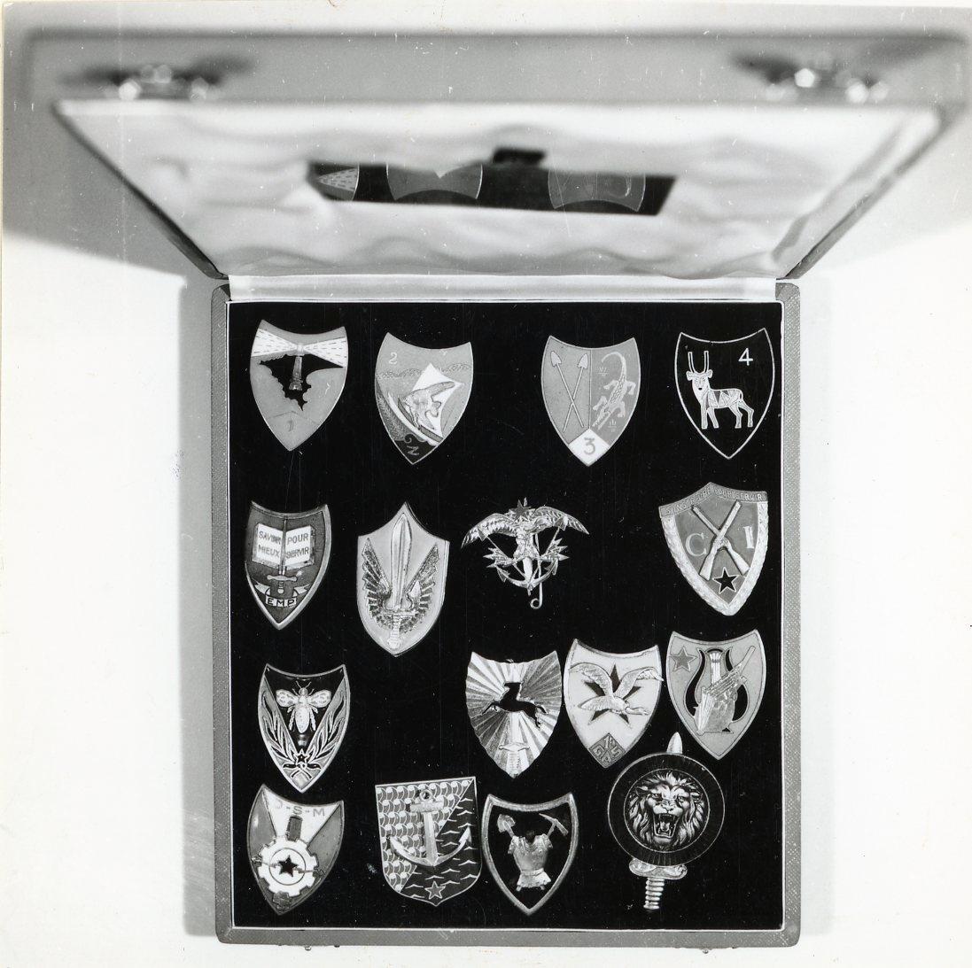 16 stycken vapenemblem i metall. 14 stycken av dem är i sköldform med olika motiv. En av dem är rund och en av dem i form av ett ankare. Emblemen representerar Senegals samltiga militära förband. Samtliga förvaras i ett etui som utvändigt är klätt med svart papper och invändigt med svart sammet och vit sidenrips. På lockets insida finns en mässingsplåt med följande text: AVEC LES KOMPLIMENTS DU GENERAL J.A.DIALLO CHEF DETAT-MAJOR GENERAL AU CAPITAINE DE VAISSEAU VICTOR TORNERHJÄLM. DAKAR DECEMBRE 1970.