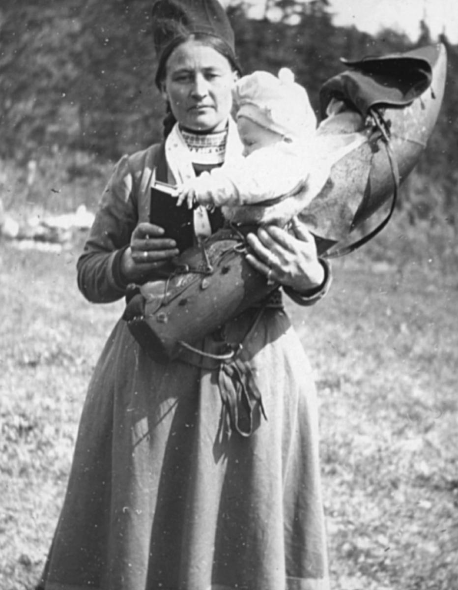 """""""N.390. Samekone fra Vefsn.N.59."""" står det på glassplaten. Portrett av samisk kvinne som står med barnet i armene.  Barnet sitter oppreist i en komse, en seng laget av en uthulet trestamme med et lokk av skinn eller lærret som kan surres fast til stammen. Komsen har også lange reimer, beregnet på å kunne henges opp i gammen eller teltet, slik at barnet kan vugges i søvn. Siden komsen har et lokk som surres fast kan barnet heller ikke falle ut av komsen når den henger. Kvinnen har på seg samisk drakt og samelue. I halsen kan man se vevde eller broderte bånd. Kvinnen holder en bok i hånden, muligens en salmebok eller en bibel? Vefsn (sørsamisk: Vaapste) er en kommune på Helgeland i Nordland Fylke."""
