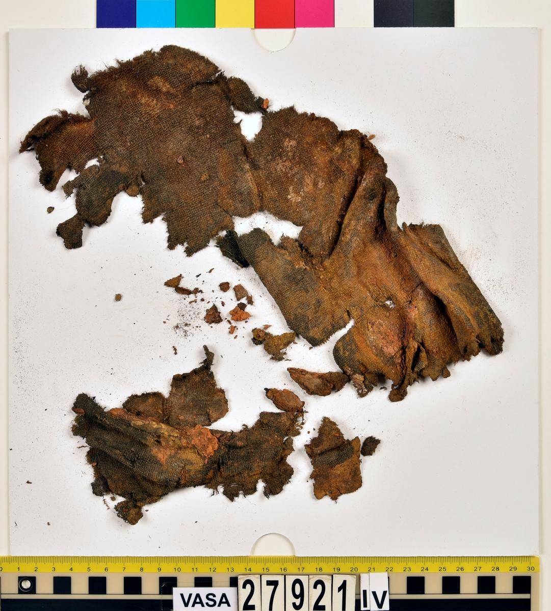 """Textil. Ca 47 textilfragment av ull vävda i tuskaft uppdelade på 27921:III-VIII. 27921:III innehåller 1 fragment. 27921:IV innehåller 6 fragment samt en del små """"smulor"""". 27921:V innehåller 2 fragment. 27921:VI innehåller ca 30 fragment. Förutom några vävda fragment är där en hel del sammanpressade fibrer. Förmodligen var textilen sönderfallen och blöt när den lades upp på lakansbiten.  27921:VII innehåller 4 fragment. 27921:VIII innehåller 4 fragment. Några fragment i 27921:VII och 27921:VIII innehåller fållar med spår av sömmar."""