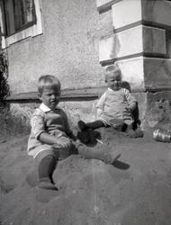 Två barn som leker i sanden på Tuna gård.