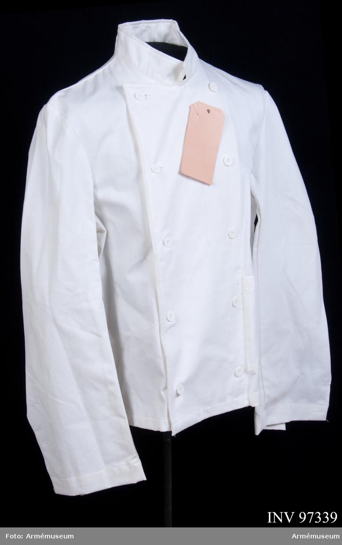 """Rock i vitt bomullstyg. Vidhängande etikett: """"Arbetsmodell på, M 7370-102000-3, Kockrock, enl. TB 17035, Näsby Park 91-11-04, Eva Rydin"""". Etikett på insidan: """"M 7370-102000-3, 1988, C 48, Tranemo textil AB, tillverkad i Portugal, 100 % bomull, skötselråd""""."""