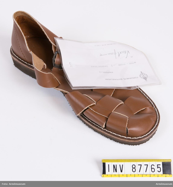 """Sandal med brunt ovanläder i flätat mönster. Svart gummisula. I innersulan är tre kronor samt storleksnumret 42 inpräglat.  Vidhängande modellapp med text: """"Försvarets materielverk. Fastställs. M 7335-151000-2 Sandaler, bruna. (oläslig underskrift)."""""""