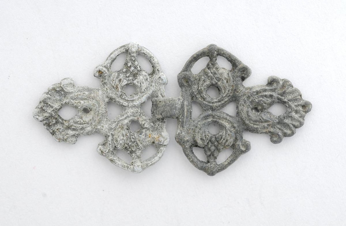 Spenne, A og B, i tinn (?), Spenna er tilnærma trekanta, med tre roser på framsida. Baksida er glatt. Manglar hekte og krampe. A er skiferfarga, B er litt kvitare .