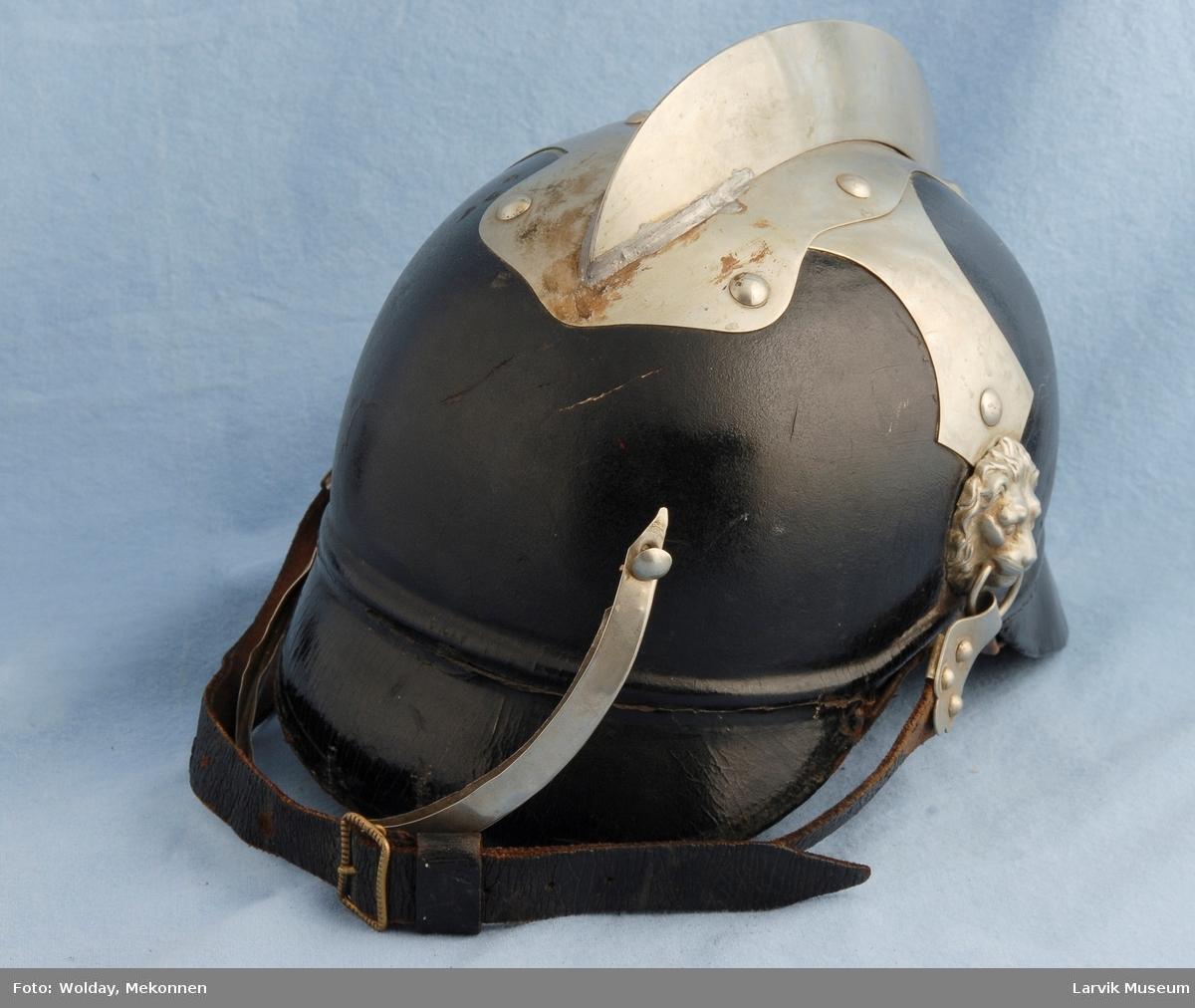"""Metall""""kam"""" over hjelmen i lengderetning, Løvehoder i metall for feste til hakerem, metallist på brem bak , bladformet beslag ved hakeremfestet"""
