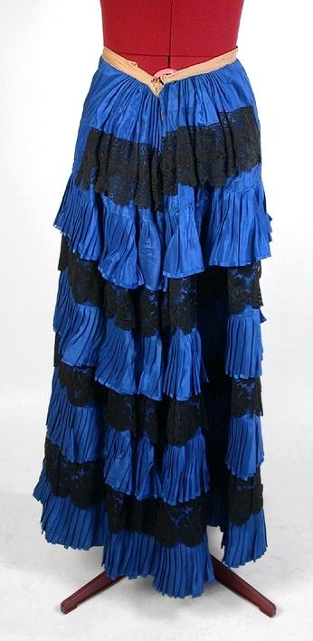 Av mörkblått siden med fyra plisserade volanger samt spetsar.
