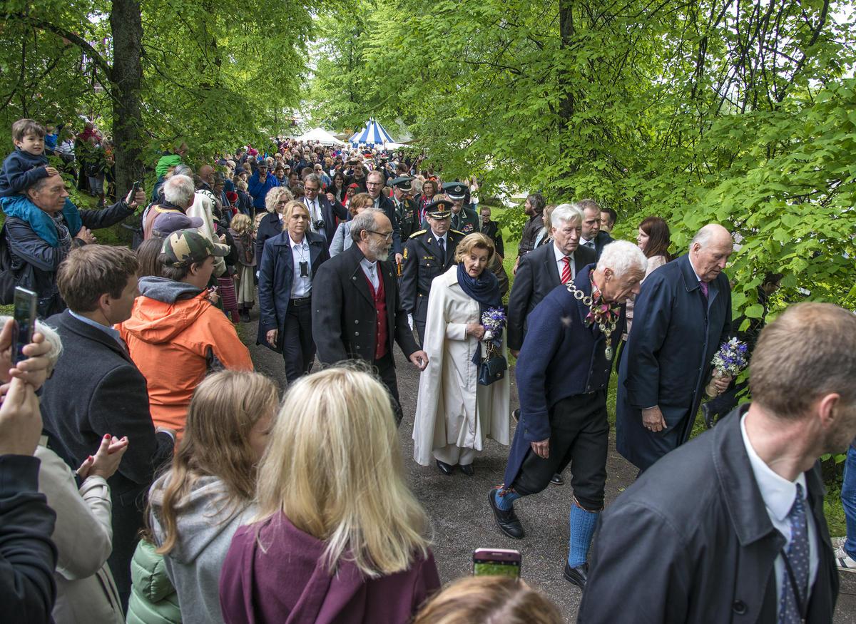 KOng Harald V og ordfører Einar Busterud i front. Dronning Sonja flankeres av Magne Rugsveen, avdelingsdirektør ved Anno Domkirkeodden (t.v.), og fylkesmann Sigbjørn Johnsen.
