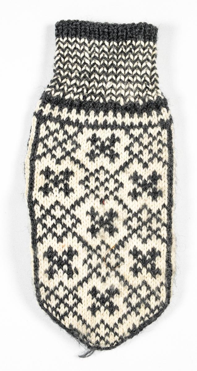 Vott, handstrikka i svart og hvitt ullgarn. Vrangbord strikka 1 rett, 1 vrang og kvit og svart annankvar omgang.