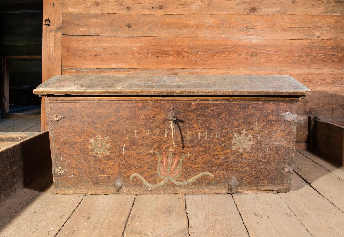 Kista av furu, rektangulär med svagt välvt lock. Brun flammig målning med enstaka blommor. Gångjärn, beslag, handtag, lås och nyckel av järn.