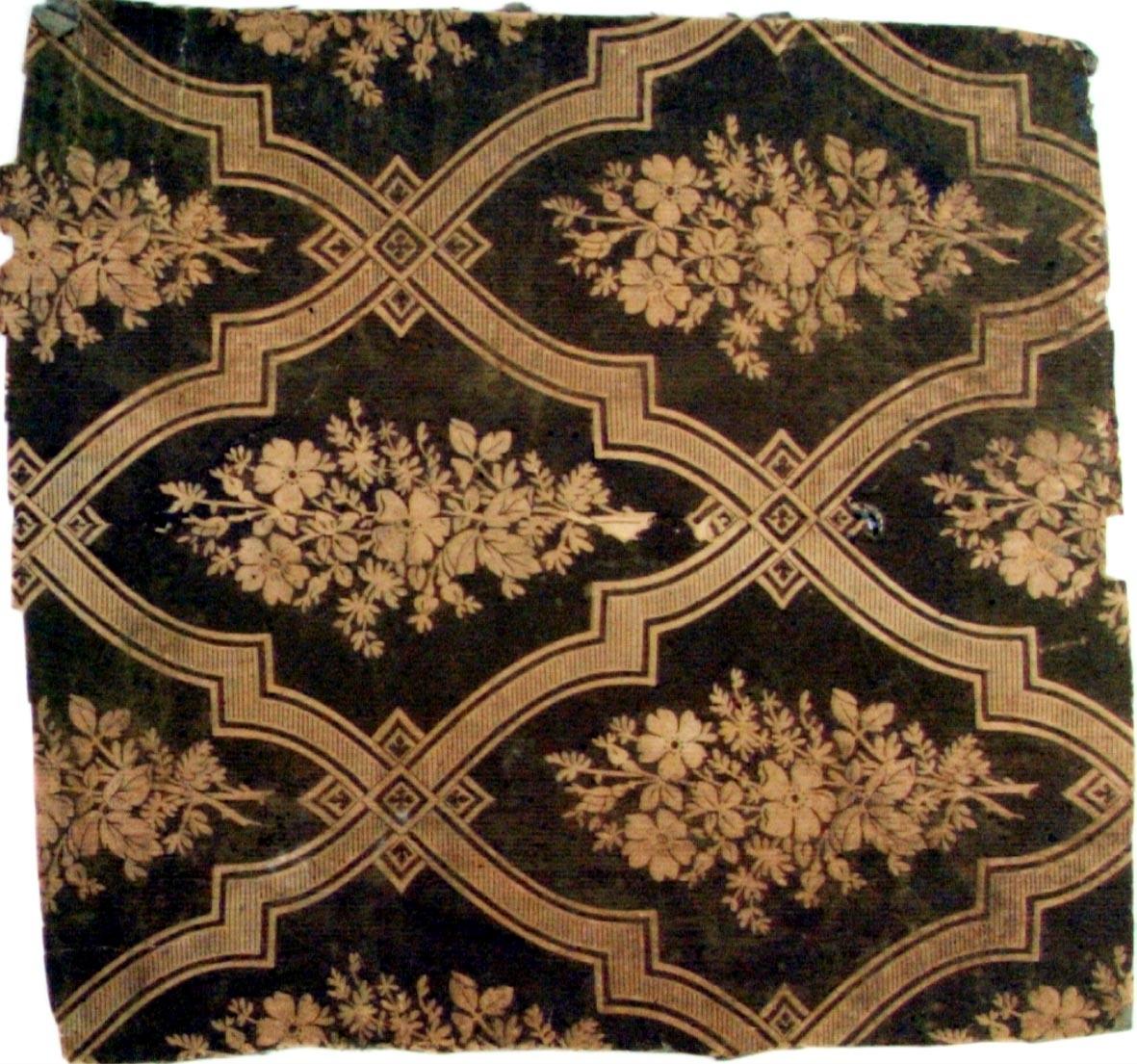 Stort snedrutmönster bestående av rombformer där själva linjen är använd som ornament. Varje mönsterdel är dekorerad med en blombukett och varje krysspunkt med ett rutornament. Tryck i brunt på ofärgat papper.