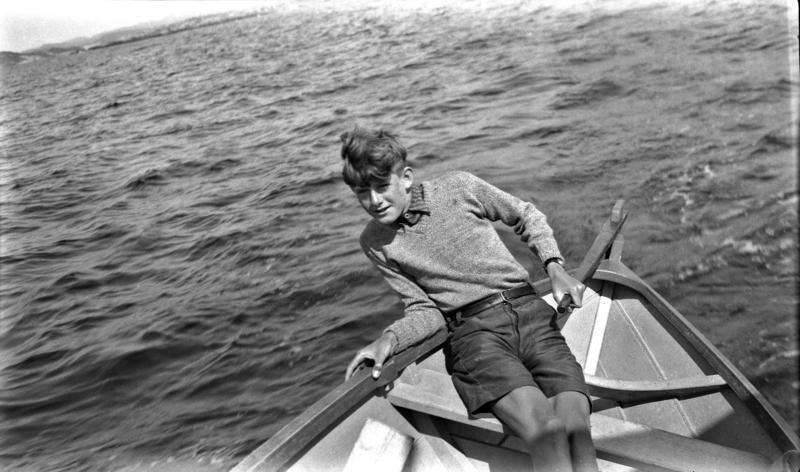 Gutt ved roret i båt