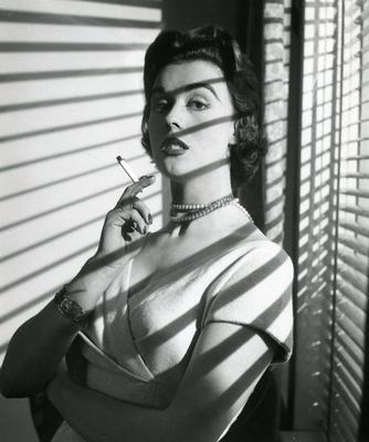 Kvinne ved vindu med sigarett i hånden.