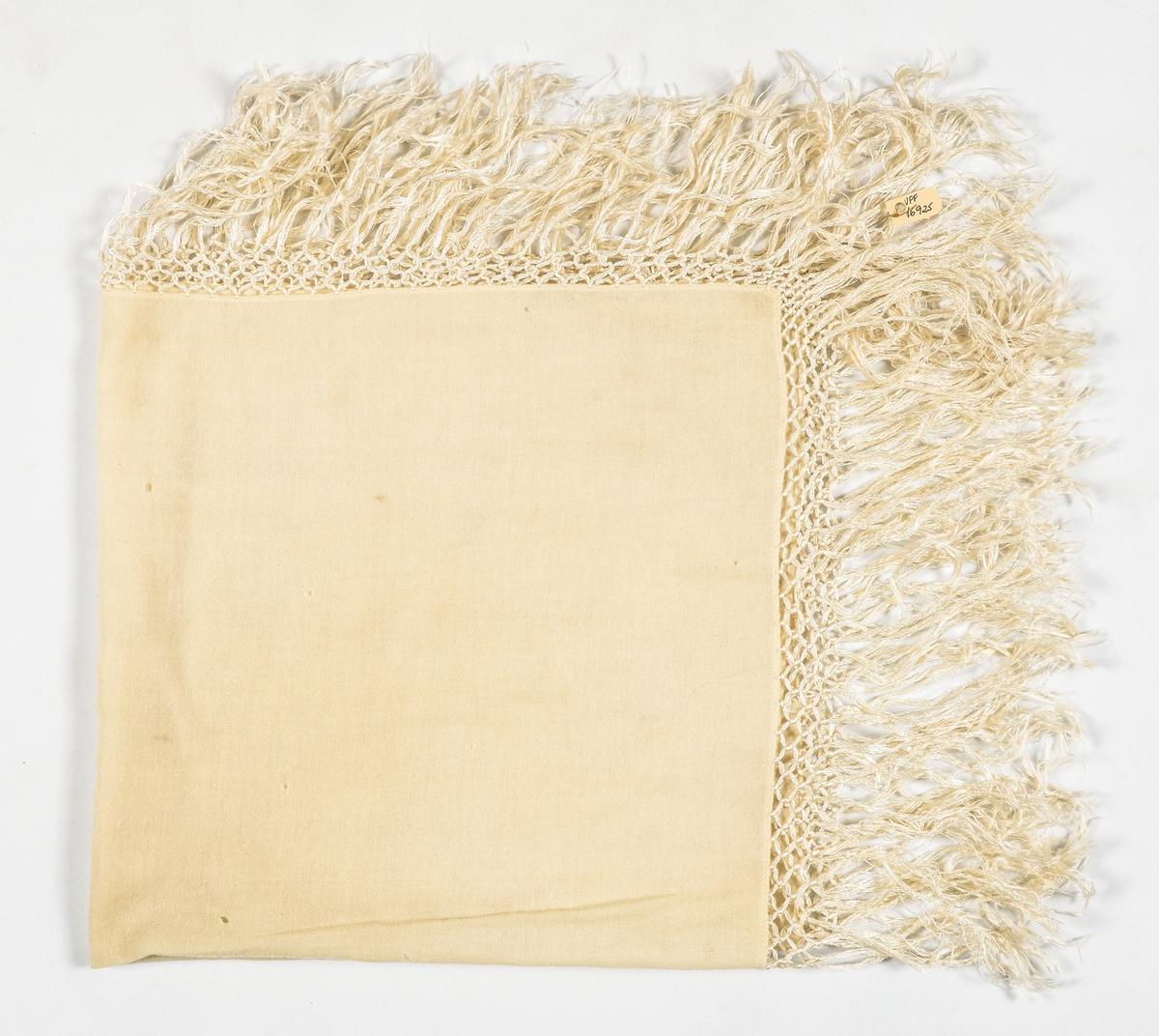 Tørkle i kremgul ullmusselin. Falda med maskinsaum. Påsette og knytta silkefrynser.
