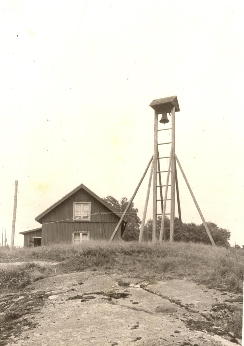 En arbetarbostad med telefonstolpe på en bergshäll.
