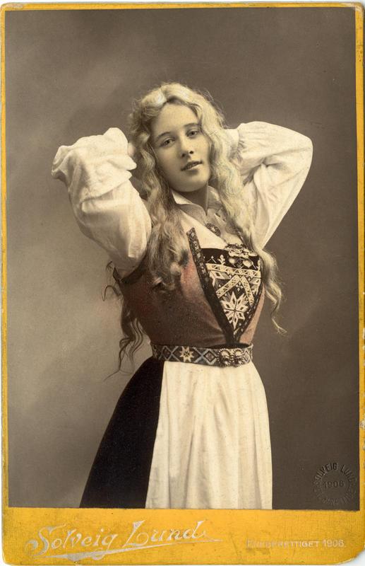 Kolorert studiofotografi av kvinne med harangerdrakt og utslått  hår. 1906.