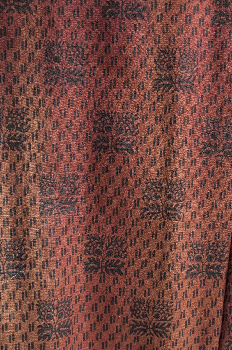 Kjole i raudbrunt (karminraudt) toskaftvove ulltøy, med svart trykt mønster. Figursydd liv med to snitt på kvar side av framstykket, svinga sidesaumar i ryggen og bakovertrekte skuldersaumar. Opning framme med  fem svarte knappar og to i metall, sju handsydde knappehol. Ei hekte i halsen og to i livet på innsida. Todelt erm med påsydde pynteband i svart fløyel framme på ermet, ein trekt knapp. Smal krage. Liver er fòra med lerret. Stakken er satt saman av  6 høgder, tre bak som er rette og tre framme er skrådde. Rynka i livet midt bak (13 cm) og med seks  faldeblad på eine sida, sju på den andre. Midt framme eit glatt stykke på 8 cm. Opning i stakken i andre folda på venstre side, lukka med hekte og hempe. Vanleg opplegg, ingen skonering.  Liv og stakk er samansydde med ein smal tittekant. Belte i same tøyet, med svart fløyelsband, eit stor sløyfe midt bak, og ei lita midt framme som også er laga av same tøyet. Stikklomme på høgre side (andre foldebladet)  i lerret. Maskinsydd for det meste, overkasting for hand.