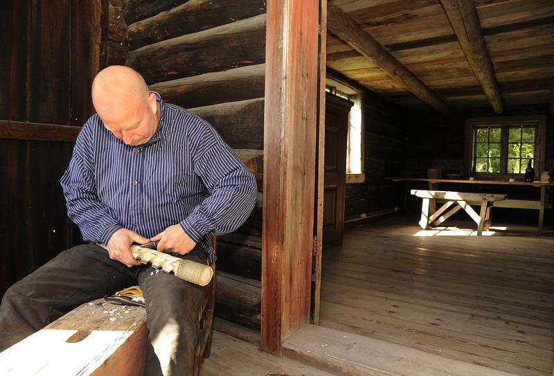 Skallet mann med buserull sitter på en svalgang på et tømmerhus og spikker.