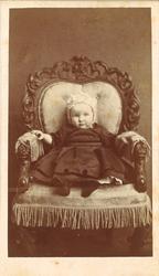 atelierfotografi av ei lita jente som sit i ein lenestol kle