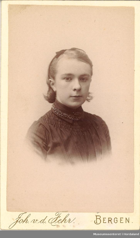 portrettfotografi av ung jente med hårband, mørk kjole og gimpa/strikka (?) band rundt halsen
