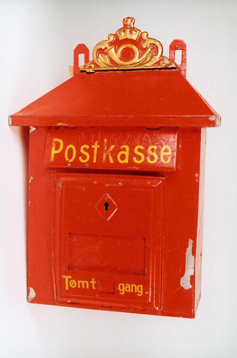 Rød postkasse utsmykket med posthorn og krone øverst på kassen. Gjenstanden har slitasjemerker i maling.