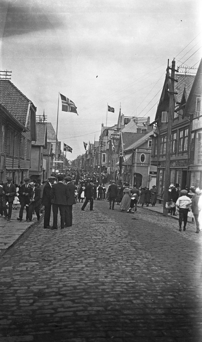 17. mai tog. Mange festkledde personer i tog med norske flagg. Tilskuere på fortauet. Hverdagsfoto.