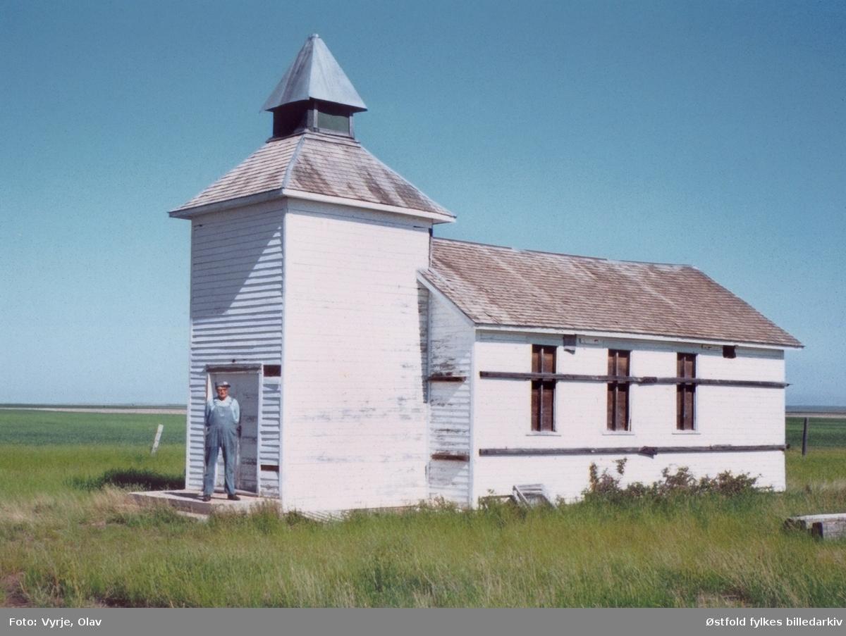 """Dry Creek Lutheran Church, Dawson County by Glendive, Montana , U.S.A. i juni 1984. Kirke på prærien som ble bygd av utvandrede søsken fra Skiptvet i Østfold. På bildet Loyd Greiman (1914-1991), sønn av Karoline Syversen gift Greiman fra Jakobshaugen i Skiptvet.  """"Dry Creek Lutheran Church i Dawson County, Montana, USA, bygget av skjetvinger.  Det var mange som reiste til Amerika fra Skiptvet. Av en søskenflokk på 10 reiste hele 7 fra Jakobshaugen søndre i Skiptvet. De to første guttene, 18 og 20 år, reiste i 1883 til Fairibault, Minnesota hvor alle havnet etterhvert. Men i 1910 tok seks av dem land i samme område øst i Montana. Noen som naboer. Her ute på prærien bygde de sin egen kirke med kirkegård, hvor utvandrerne og deres etterkommere er blitt gravlagt. Slektenes kirkegård er fortsatt i bruk. Men av praktiske grunner ble kirken i sin tid flyttet fram til en kjørevei. Da loven kom at engelsk skulle være det eneste offisielle språk i skoler og ellers, og med en økende intergrering, ble kirken til slutt solgt og tatt i bruk som kornlager. Etter noen år raste den helt sammen i 1985. Foto fra 1984."""" Olav Vyrje, 2008, skrev denne teksten til kalenderbilde for Skiptvet historielag i 2008 (desember). Han har også fotografert kirken."""
