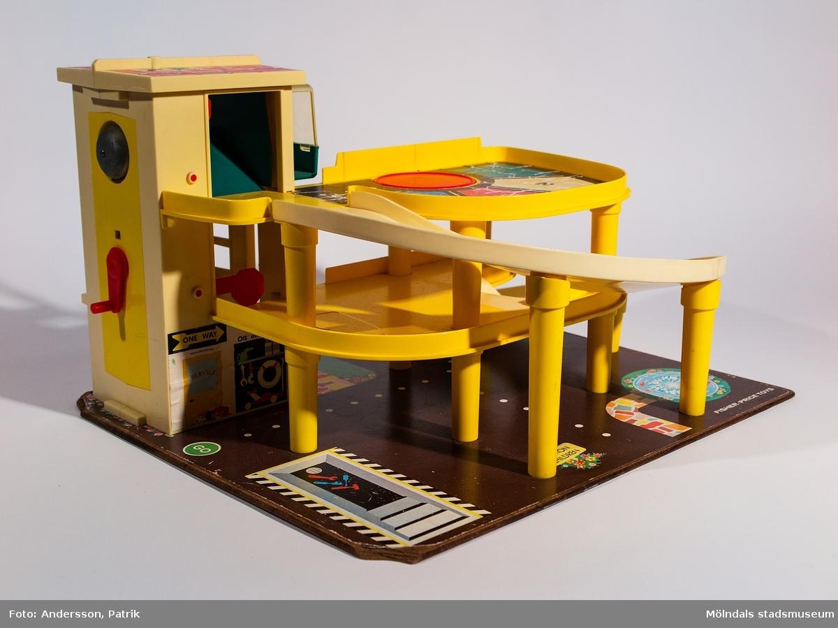 Fisher-Pricegarage från 1970-talet. Inköpt 2001 på Second Hand av givaren, vars barn har lekt med det. Garaget är i tre plan och står på en masonitplatta. Det har person-/bil-hiss med vevfunktion och pling från plan 1-3, vev att snurra vänd-platta på våning 3, tankstation på plan 1 samt två nedförsbackar från plan 2 och 3 till plan 1. Nivåskillnaderna är uppbyggda med plaststolpar vilket gör att bilar lätt åker nedför backarna.