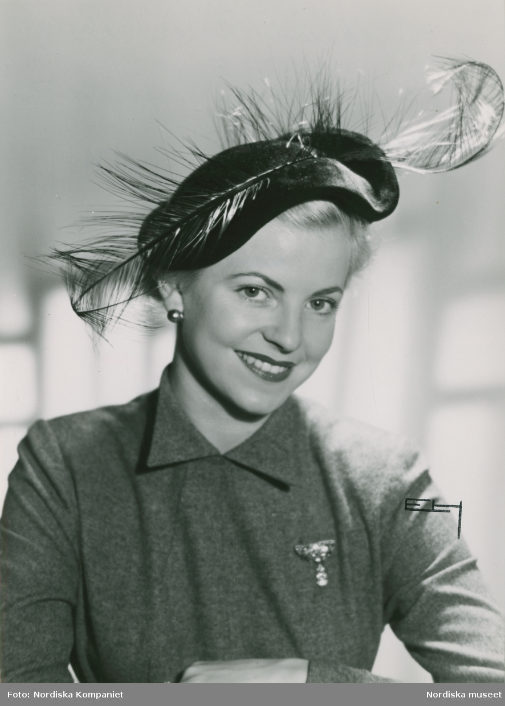 Porträtt av modell i hatt av svart velour med svarta strån, samt brosch och örhänge.