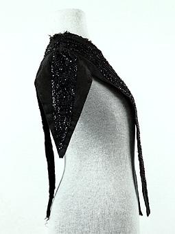 Del av klädningsliv sytt av svart ripsvävt siden, dekorerat med bårder av svarta pärlbroderier. Troligen är pärlorna av glas.