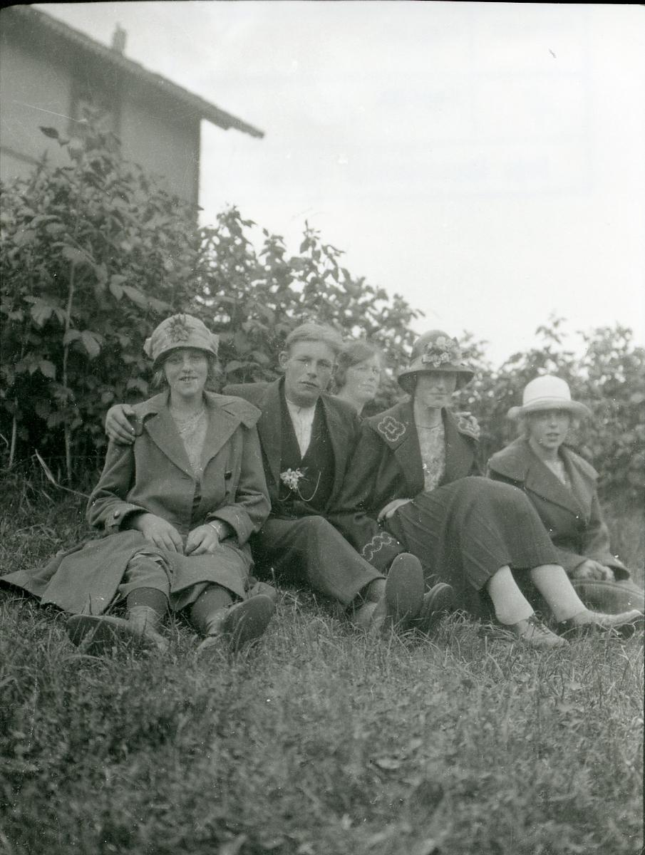 4 kvinner og en mann sitter på grasbakken foran et hus.