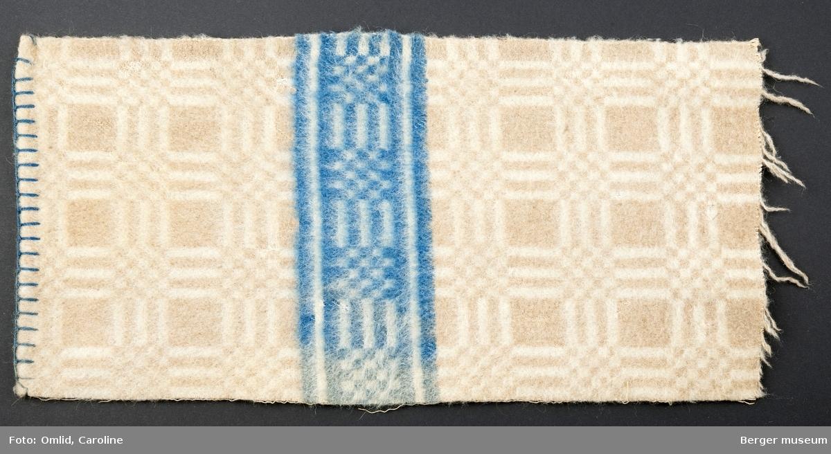 teppe med geometrisk rutemønster i lys beige og off-white, med tverrgående bord i blått.