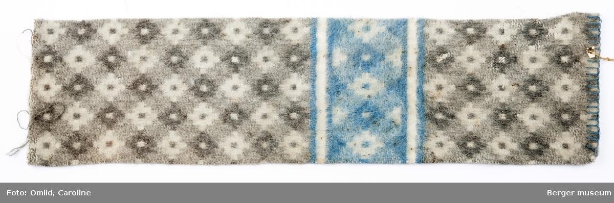 En prøve. Teppe i snipp-mønster med en mørk prikk midt i hver rute. Mønsteret blir brutt av samme mønsterbord  i en annen farge. Hyssingrest fra en merkelapp sitter fremdeles igjen på den oppsydde kanten.  Skitten, blant annet med eksrementer fra mus.
