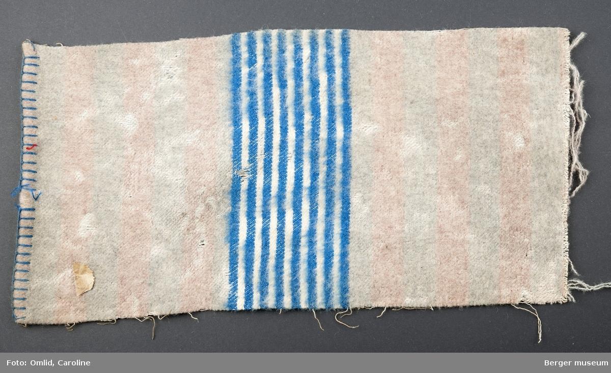 En prøve. Teppe med stripemønster i teppets bredde. Bord i åtte blå og hvite striper. Noe skitten.