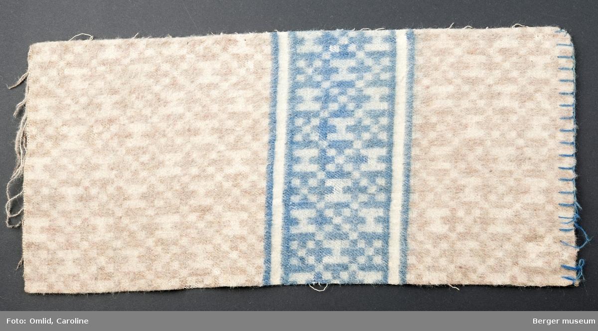 En prøve. Teppe med mønster, brutt av en tverrgående bord i blått.  Noe skitten.