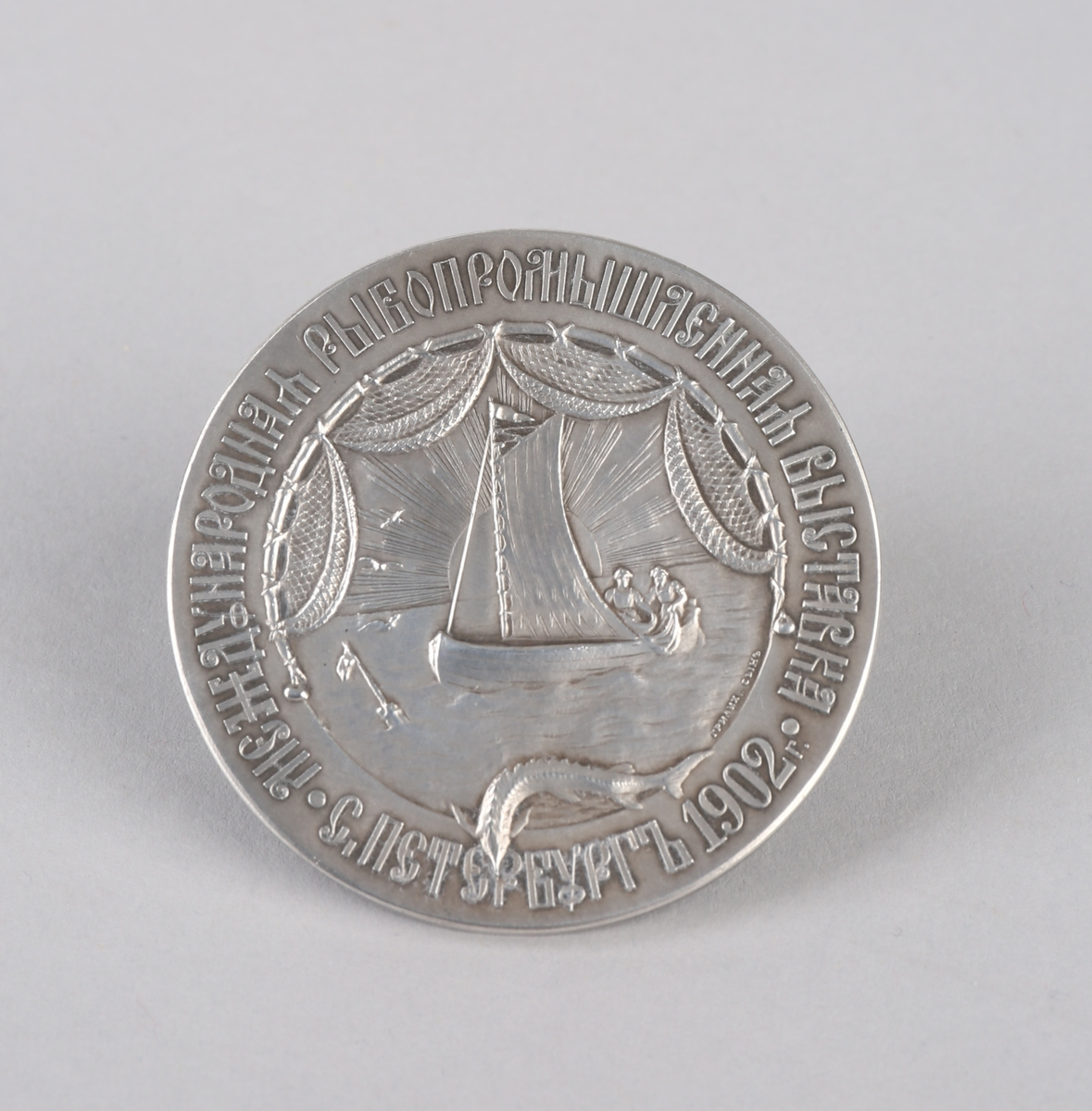 Russisk medalje fra 1902 med motiv av seilfartøy med to personer ombord som setter garn/trekker garn, russisk våpenskjold, samt tekst. Ligger i liten eske.