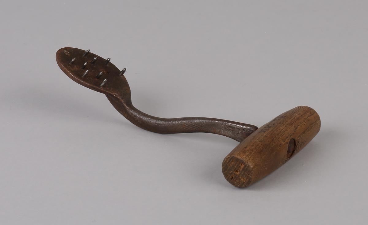 Sekkekrok/huk (lasteverktøy) i jern med ovalt endestykke med 9 spisse tenner i jern (1 stk. tann mangler). Med håndtak i tre.