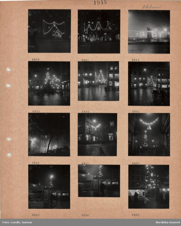 Motiv: Stockholm, gata i kvällsmörker med tända juldekorationer, Slussen, ryttarstaty, tänd gatubelysning, gata med flerbostadshus, träd, stenlagd gata med tänd juldekoration, torg med salustånd, Stortorgets julmarknad, hög julgran med tänd belysning.