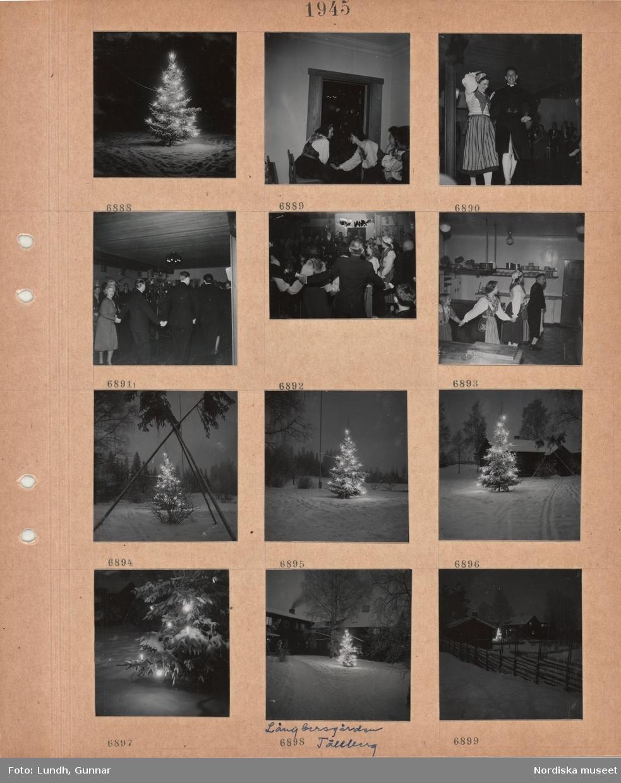 Motiv: Dalarna, julgran utomhus i snö med tänd belysning, kvinnor i folkdräkt, dansande par i folkdräkt, vuxna dansar ringdans runt julgran, personer i folkdräkt dansar långdans genom kök, julgran i snö samt tre avkvistade granstammar med toppruskor ställda i trekant, Långbersgården, Tällberg, julgran vid byggnader i snö, trägärdsgård.
