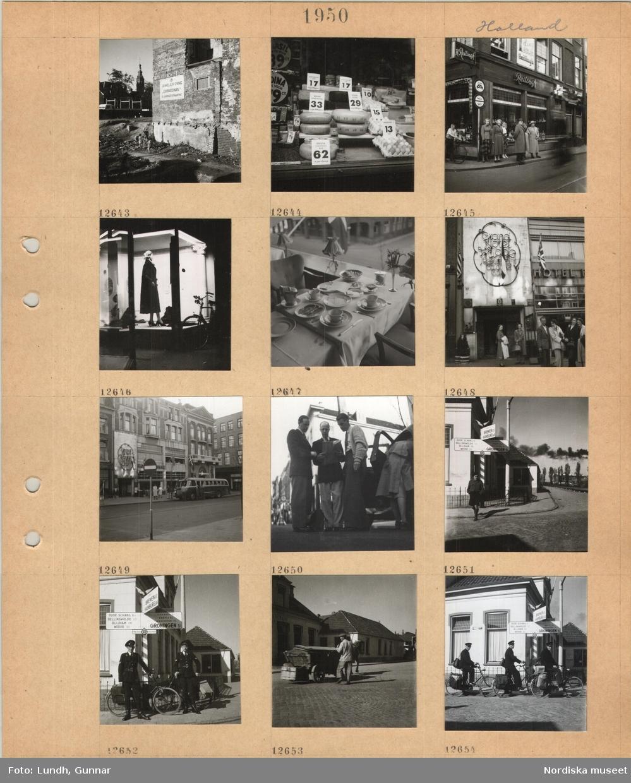 Motiv: Holland, barn vid en husruin, skyltfönster med ostar och ägg, personer står på en trottoar, butiksfasad, skyltfönster med damkläder, restaurang, bord med vit duk med frukost framdukad, resande framför ett hotell, svensk turistbuss parkerad framför ett hotell, olika nationsflaggor, tre män tittar på en karta(?), gathörn med vägskylt med avstånd till olika orter, två män i uniform med cykel i gathörn, brevbärare(?), man vid hästdragen kärra på gata, tre brevbärare i uniform med cykel och väskor.