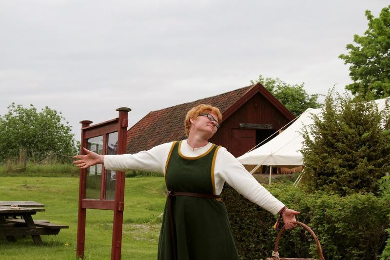 Rødhåret kvinne i middelalderdrakt, med kurv i hånda, slår ut med armene for å ønske velkommen til Urtehagen (Foto/Photo)