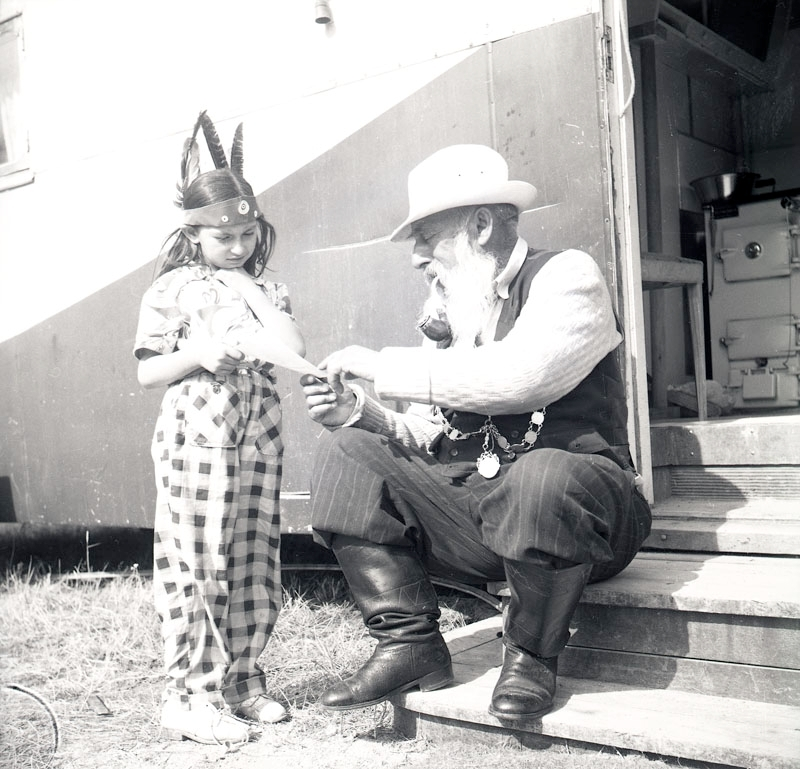 """Fotografiet är taget i juli 1952 i samband med skolundervisning i det romska lägret i Ekeby, ca 4 km väster om Eskilstuna. En flicka med fjädrar i håret läser från ett papper tillsammans med en äldre man. Lärarinnan som vanligtvis undervisade i Göteborg, var denna sommar där på uppdrag av Stiftelsen svensk zigenarmission för att lära barnen i lägret att läsa och skriva mellan 15 juli till 15 augusti. I en lärarrapport från september samma år har lärarinnan beskrivit sitt första möte med lägret i Ekeby med följande målande beskrivning: """"Redan när jag den 15 juli kom till lägret stod skoltältet färdigt placerat mellan två bostadsvagnar. Sex stycken av Eskilstuna stad kasserade skolbänkar fyllde upp skolrummet. På ena kortsidan var en likadan av Eskilstuna stad kasserad liten svart tavla uppspikad."""" Lärarinnan berättar i rapporten om undervisningen: """"På de små skolbänkarna satt elever av olika åldrar som besökte skolan varje dag. De barn som tillhörde skolpliktig ålder var sex till antalet och alla flickor. Fyra av dem hade inga kunskaper i läsning och skrivning."""" Även lägrets yngre barn besökte skoltältet då och då. Ofta inleddes dagen med att torka av bänkarna som blivit blöta av nattens regn. Tältduken var inte av en sådan kvalitet att det höll skyfall ute. Efter en månads undervisning kunde lärarinnan konstatera att de flesta av eleverna kunde läsa enkel läsebokstext och började lära sig att räkna.  Undervisningen störs ibland av oväntade händelser. Den 9 augusti fick lägrets medlemmar besked från Drätselkammaren i Eskilstuna om att deras kontrakt löpt ut och att de måste flytta innan skolan är över. Efter en annan polismästares bedömning blev flytten uppskjuten.   Lärarinnan sammanfattar sina upplevelser i Ekeby så här: """"Från första stund möttes jag av lägrets alla invånare med den största vänlighet. Föräldrarna var alltid ivriga då det gällde att sända sina barn till skolbänken. Vilka fördomar låter vi inte frodas omkring en minoritet, bara därför att den är olik"""
